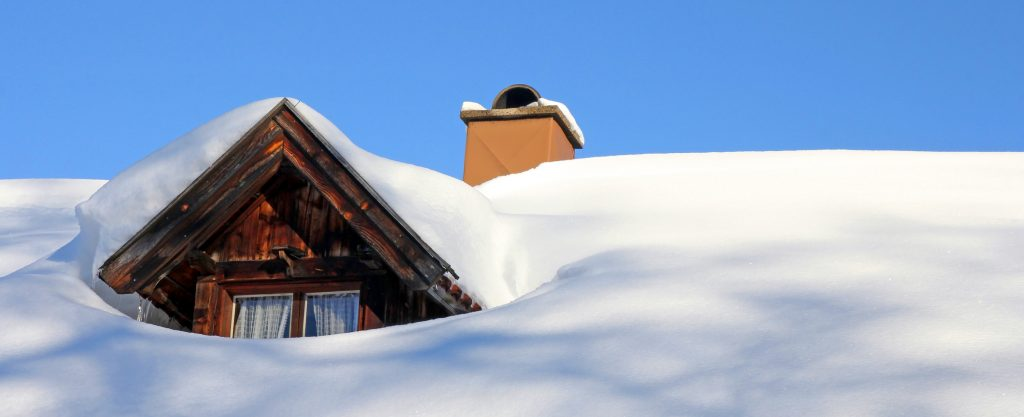 A snowed roof window of an old wooden house